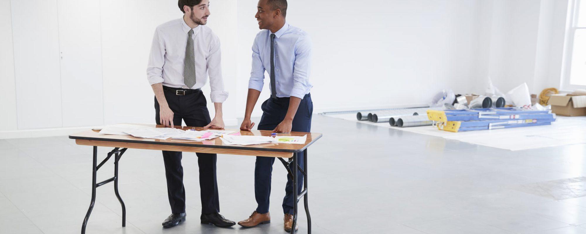 businessmen-discussing-plans-for-office-interior-PHE9RJM-min